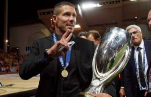 Atletico Madrid's coach Simeone holds the trophy as he  celebratesbtheir win against Chelsea in their Super Cup soccer match at Louis II stadium in Monaco